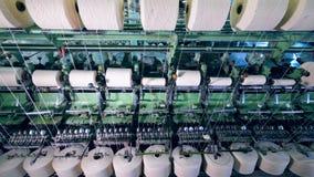 De witte spoelen worden gekronkeld door textielmateriaal stock video