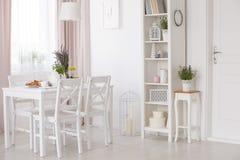 De witte stoelen en de lijst met bloemen onder lamp in eetkamerbinnenland met lavendel bloeien Echte foto royalty-vrije stock foto