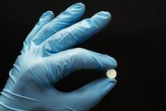 De witte tablet in dient een blauwe handschoen op een zwarte achtergrond, concept in stock afbeeldingen