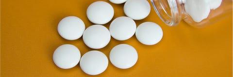 De witte tabletten zijn verspreid van een glasfles stock afbeeldingen