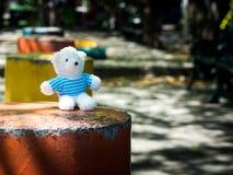 De witte teddybeer draagt een blauwe overhemd en een zitting op oranje bank met cement de achtergrond is openbaar park Exemplaarr stock fotografie