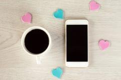 De witte telefoon met een kop van koffie en de kleine harten liggen op een witte houten lijst stock fotografie