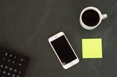 De witte telefoon met een kop van koffie, een rode pen en een calculator liggen op een witte houten lijst stock foto