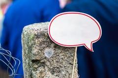 De witte toespraakwolk met exemplaarruimte op een stok maakte aan een oude concrete kolom op de achtergrond van mensen in blauwe  stock fotografie