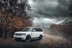 De witte tribune van Rover Range Rover van het autoland op platteland off-road bij dramatische wolkendag Stock Fotografie