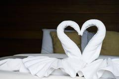 De witte vouwenhanddoeken zoals zwaan bepalen op het bed Royalty-vrije Stock Fotografie