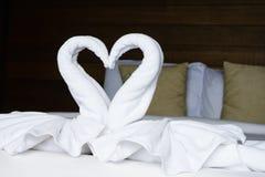 De witte vouwenhanddoeken zoals zwaan bepalen op het bed Stock Foto