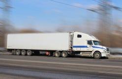 De witte vrachtwagen drijft langs de weg Stock Fotografie