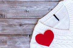 De witte vrouwelijke sweater, trui met rood hart op het op uitstekende houten achtergrond met vlakke exemplaarruimte, legt stock foto's