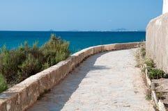 De witte weg van de steenbestrating langs rotsachtige kust. stock fotografie