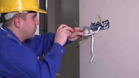 De witte werknemer meet het elektrocontactdoosvoltage stock footage