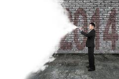 De witte wolk die van de zakenmannevel de oude donkere bakstenen muur van 2014 behandelen Stock Foto