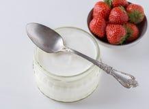 De witte yoghurt in glaskom met lepel op bovenkant en starwberries is Royalty-vrije Stock Fotografie