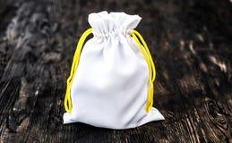 De witte zak van de stoffengift op donkere houten achtergrond Royalty-vrije Stock Fotografie