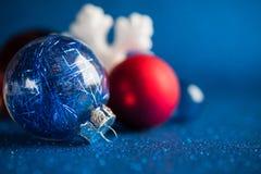 De witte, zilveren en rode Kerstmisornamenten op donkerblauw schitteren achtergrond Stock Afbeelding