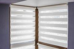 De witte zonneblinden van de stoffenrol op het plastic venster met houten textuur in de woonkamer met blauwe muur stock foto