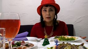 De woedende volwassen vrouw in een rode kleding en een rode hoed schreeuwt en zweert in een koffie of een restaurant stock video