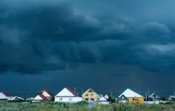 De Wolken van de onweersregen over Dorpshuizen stock afbeelding