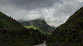 De wolken zwemmen langzaam onder de bergachtige groene toneelpieken stock video