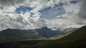 De wolken zwemmen langzaam onder de groene bergen van de Kaukasus en ijs toneelpieken in de zomerzonsopgang Zonlichten en schaduw stock footage