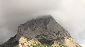 De wolkenflarden van de tijdtijdspanne rond en over bergpiek, Berg koba-Kaya stock video