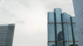 De wolkenkrabbers van het close-upglas bij daglicht, hemelbezinning bij voorgevels collectieve gebouwen stock video