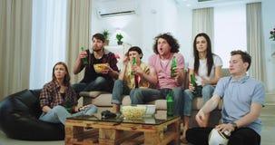 In de woonkamer op bank is de groep vrienden die op geconcentreerde voetbalwedstrijd letten en verstoord die hun voetbal stock video