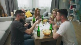 In de woonkamer spelen de vrienden geeks een strategisch raadsspel stock videobeelden
