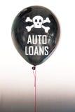 De woorden autoleningen in wit en schedel en dwarsbeenderen op een ballon die het concept een schuldbel illustreren Stock Fotografie