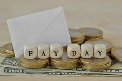 De woorden betalen dag met houten kubussen over muntstukken en dollarbankbiljetten dat wordt geschreven stock fotografie