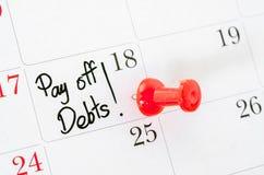 De woorden betalen geschreven Schulden stock afbeeldingen