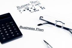 De woorden van het businessplan dichtbij glazen, calculator en pen, bedrijfsconcept Royalty-vrije Stock Foto's