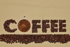 De woordkoffie van koffiebonen met een kop geurige hete koffie op een lichtbruine achtergrond 1 Stock Foto