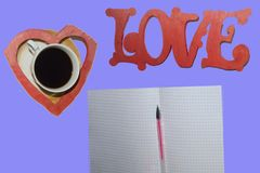 De woordliefde, een Kop van koffie, een hart, een blad met een pen stock afbeelding