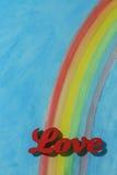 De woordliefde met een kleurrijke regenboog en een blauwe hemelachtergrond Stock Foto's