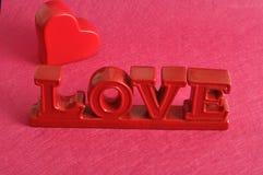 De woordliefde met een rood hart Stock Foto's