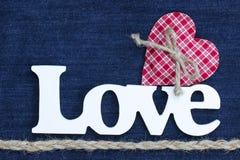 De woordliefde met rode hart en kabelgrens op denimachtergrond Royalty-vrije Stock Fotografie