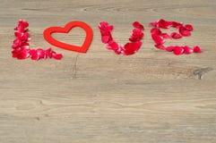 De woordliefde met roze bloemblaadjes wordt gespeld dat Stock Foto