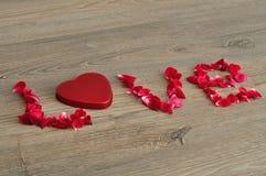 De woordliefde met roze bloemblaadjes wordt gespeld dat Royalty-vrije Stock Foto's