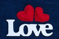 De woordliefde met twee rode harten op denimachtergrond Stock Fotografie