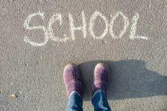 De woordschool op het asfalt en de voeten van de student royalty-vrije stock foto