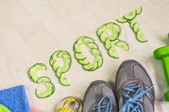 De woordsport is gevoerd met komkommers, tegen de achtergrond van tennisschoenen, domoren en een handdoek Stock Foto's