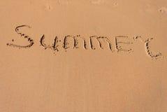 De woordzomer die in het zand op een strand wordt geschreven Stock Fotografie