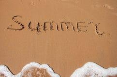 De woordzomer die in het zand op een strand wordt geschreven Stock Foto's