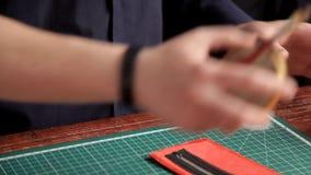 In de workshop, lijmt een mens de werkstukken van de huid, makend een portefeuille stock videobeelden