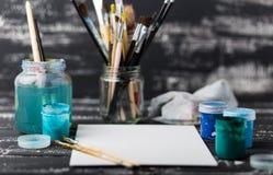 De workshop van de kunstenaar `s Canvas, verf die, borstels, paletmes op de lijst liggen Kunsthulpmiddelen De achtergrond van de  stock fotografie