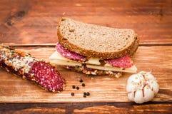 De worst kookte gerookte worst, kaas met dark voor ontbijt, sandwich, zwart brood, knoflook, zwarte peper, laurierblad op de lijs stock foto's
