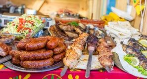 De worsten, kebab, braadden vissen en ander voedsel bij het festival van het straatvoedsel stock foto