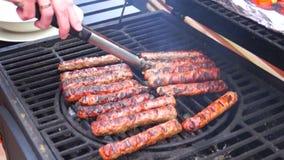 De worsten van mensengebraden gerechten op de grill stock video