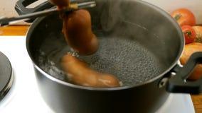 De worsten zijn aan lager en in een open pan van kokend water op elektrisch fornuis gekookt stock videobeelden